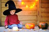 Little wizard playing with halloween pumpkins