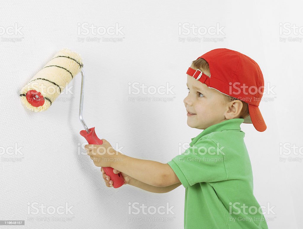 Little worker with paintroller in hands near white wall royalty-free stock photo
