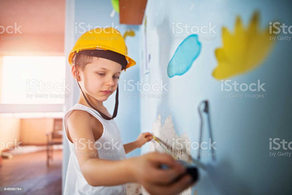 Little workers measuring damaged plaster in his room stock photo