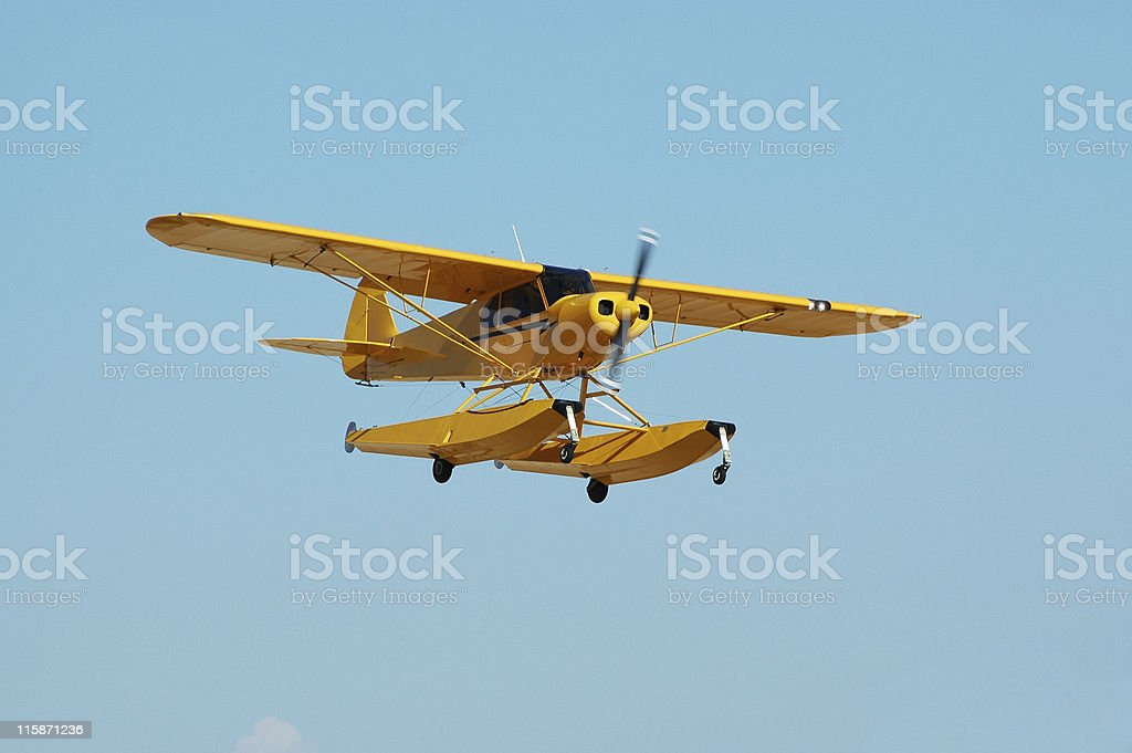 little yellow seaplane Piper Cub flying in clear blue sky stock photo