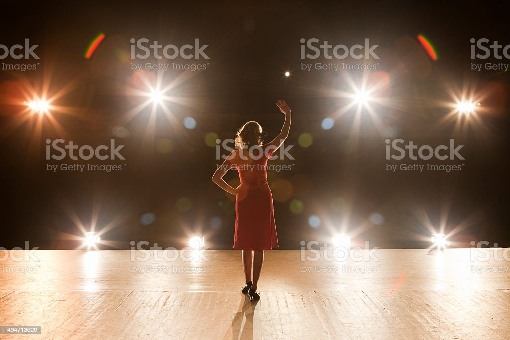 Live Performer Standing on Stage with Lights stock photo