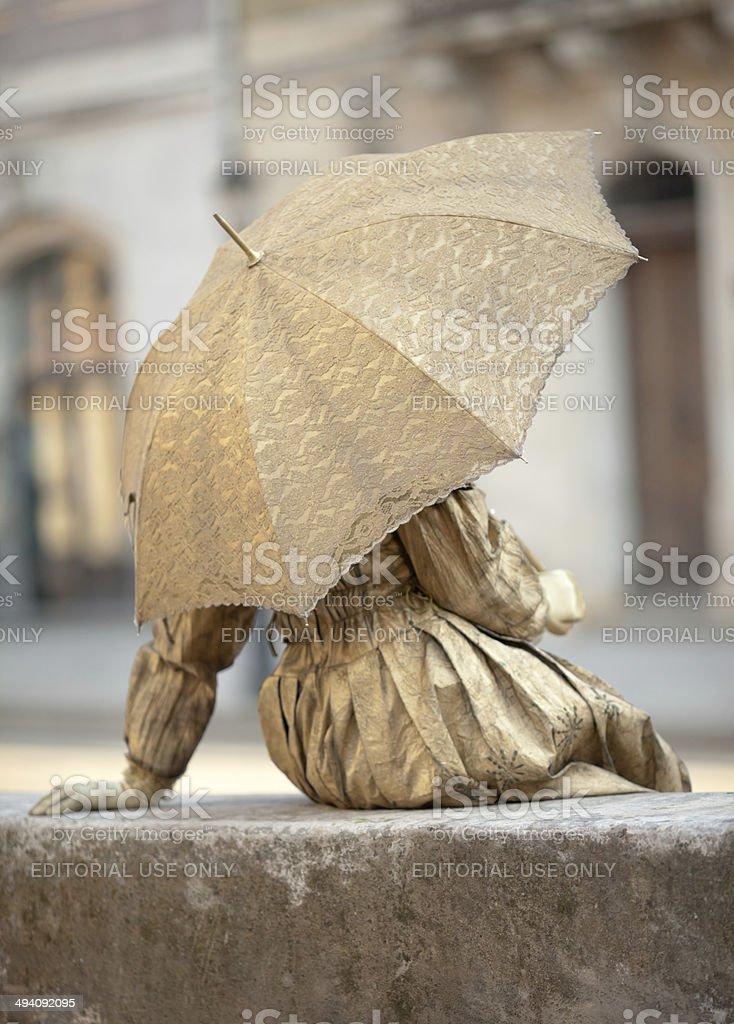 Live statue under umbrella stock photo
