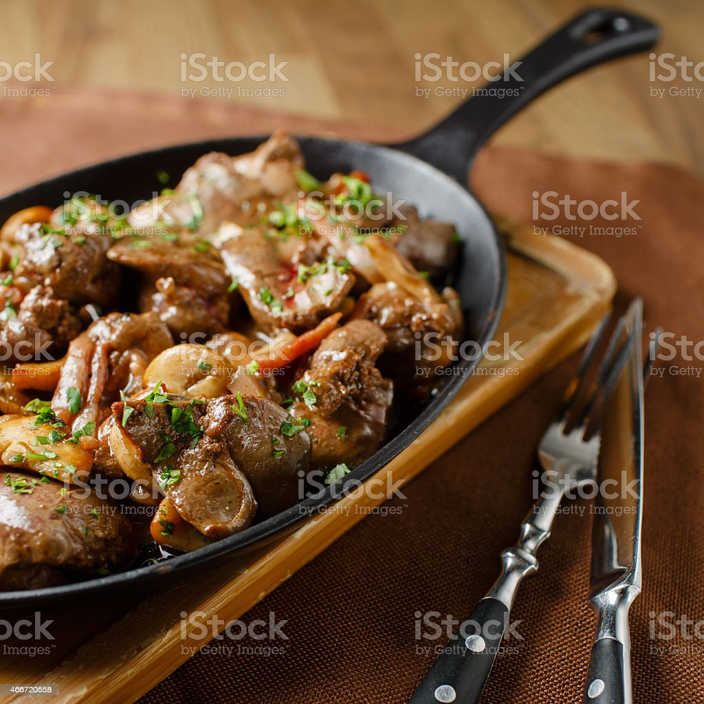 Liver baked with mushrooms, bacon and herbs stock photo