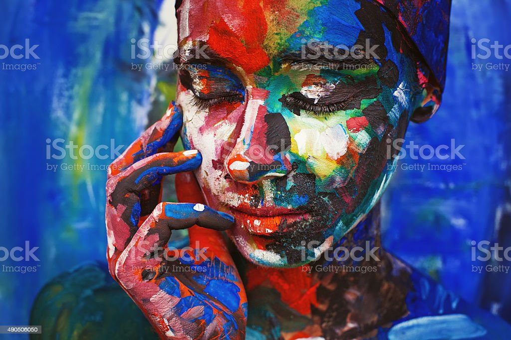 Living painting - young woman completely covered with thick paint stock photo