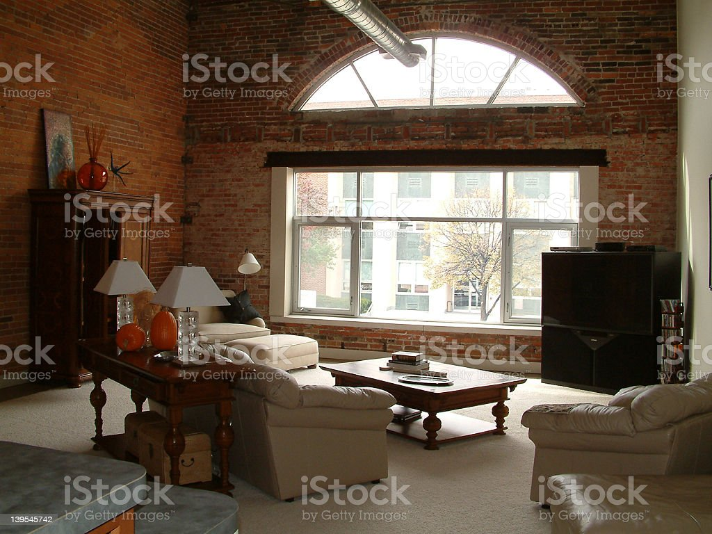 Living room in a brick walled loft room with large window royalty-free stock photo