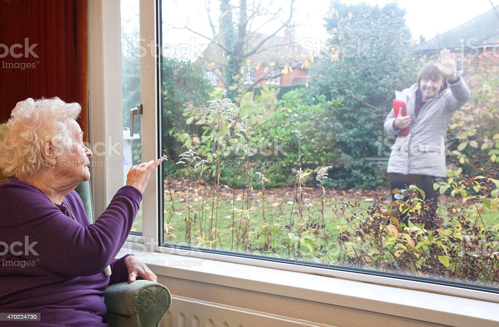 Living with dignity independently - elderly client waving goodbye stock photo