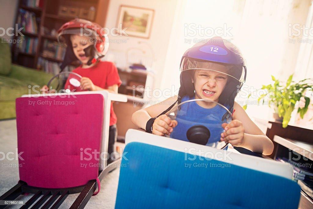 Livingroom race - little boys pretending to ride race cars stock photo