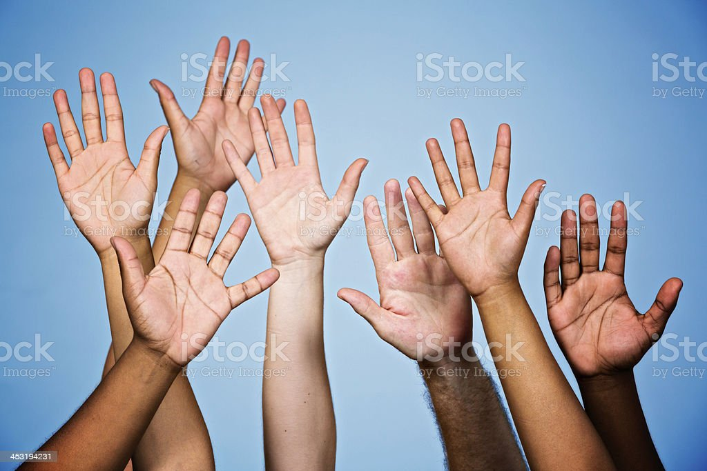 I'll do it! Many mixed raised hands volunteering or responding stock photo