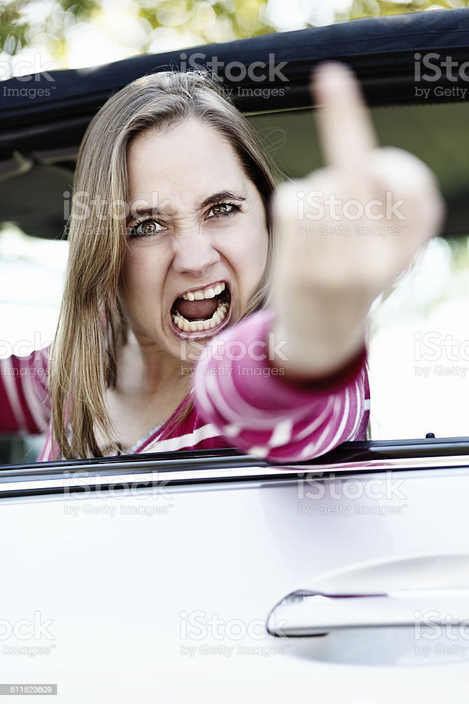 I'll get you! Furious woman driver makes obscene gesture stock photo