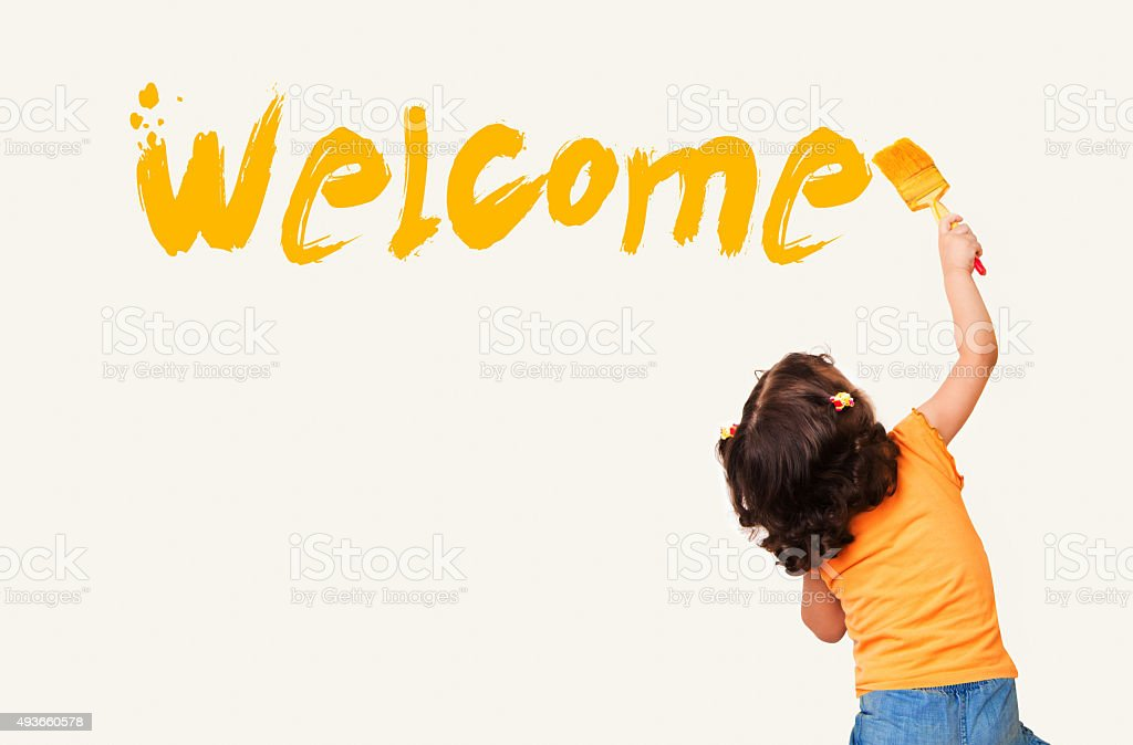 Llittle girl painting 'Welcome' on wall background stock photo