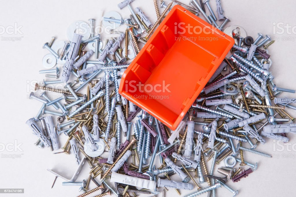 Lo of screws, bolts and dowels with orange container. stock photo