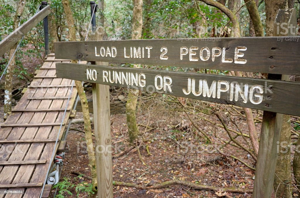 Load limit two people no running jumping sign by bridge stock photo