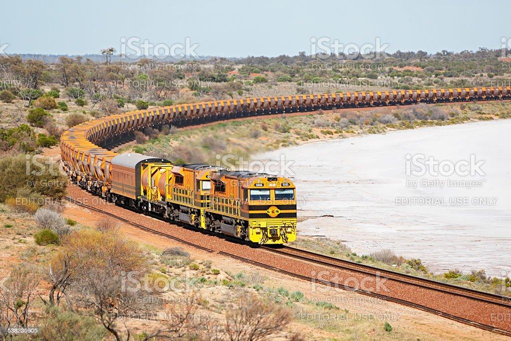 Loaded Arrium iron ore train passing outback salt lake stock photo