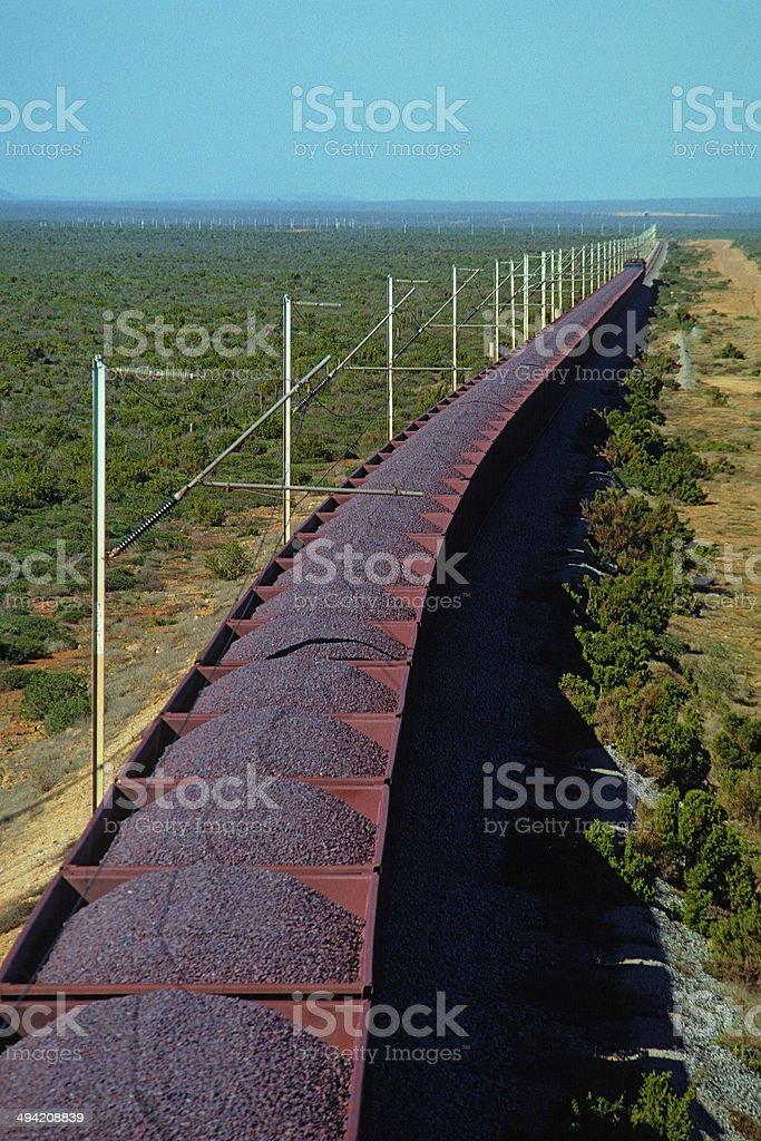 Loaded iron ore train on remote electrified railway stock photo