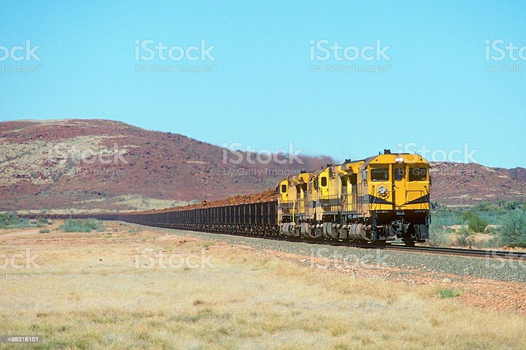 Loaded iron ore train with rugged stony hills stock photo