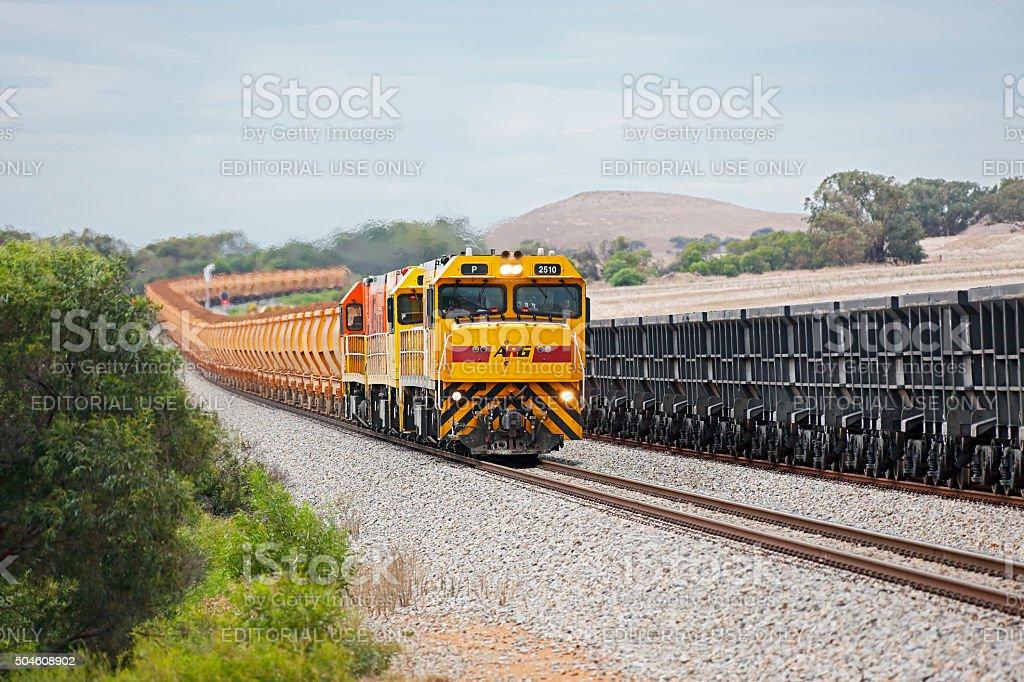 Loaded Mt Gibson iron ore train passing empty Karara wagons stock photo