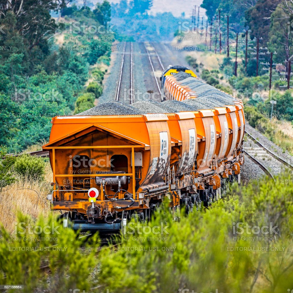 Loaded stone train with graffiti vandalism in rural countryside stock photo