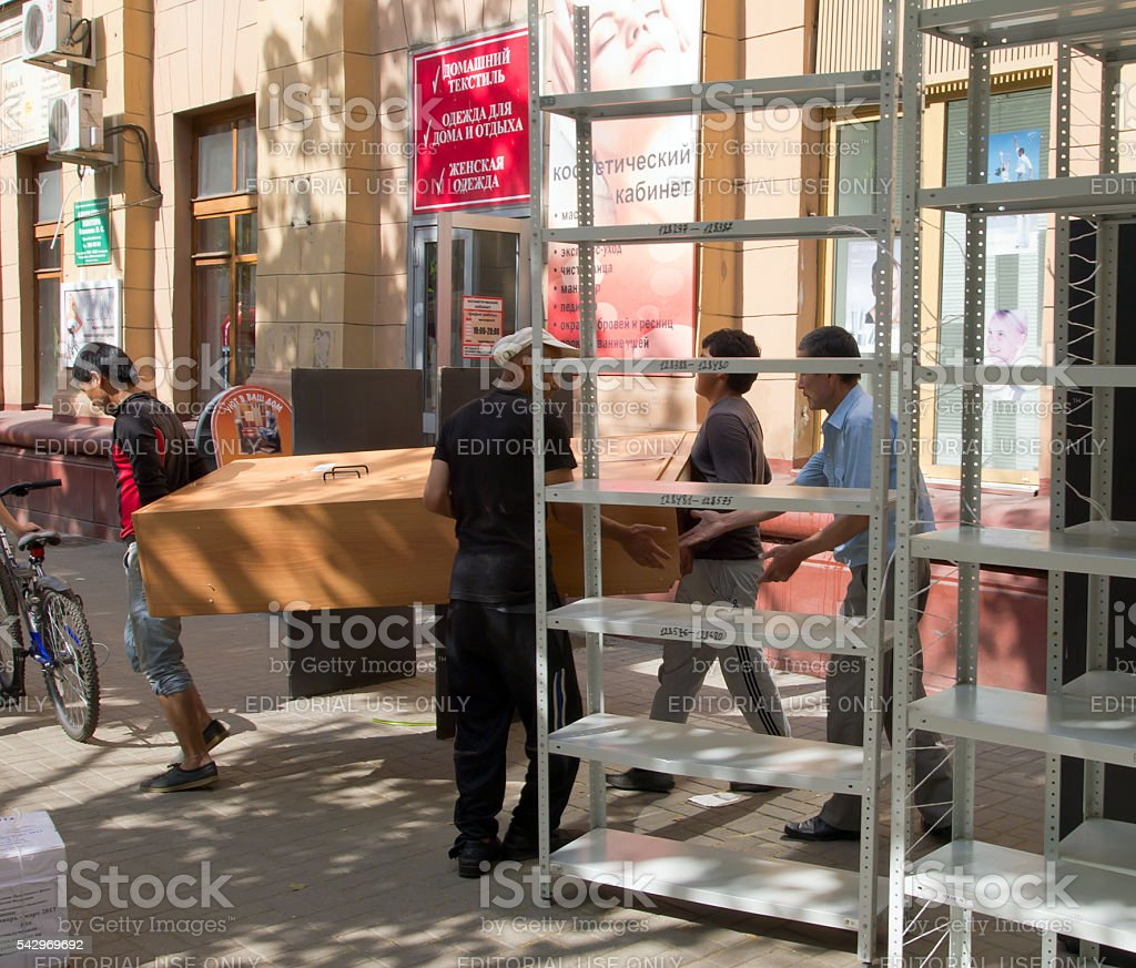 Loaders carry things on the street during an office relocation stock photo