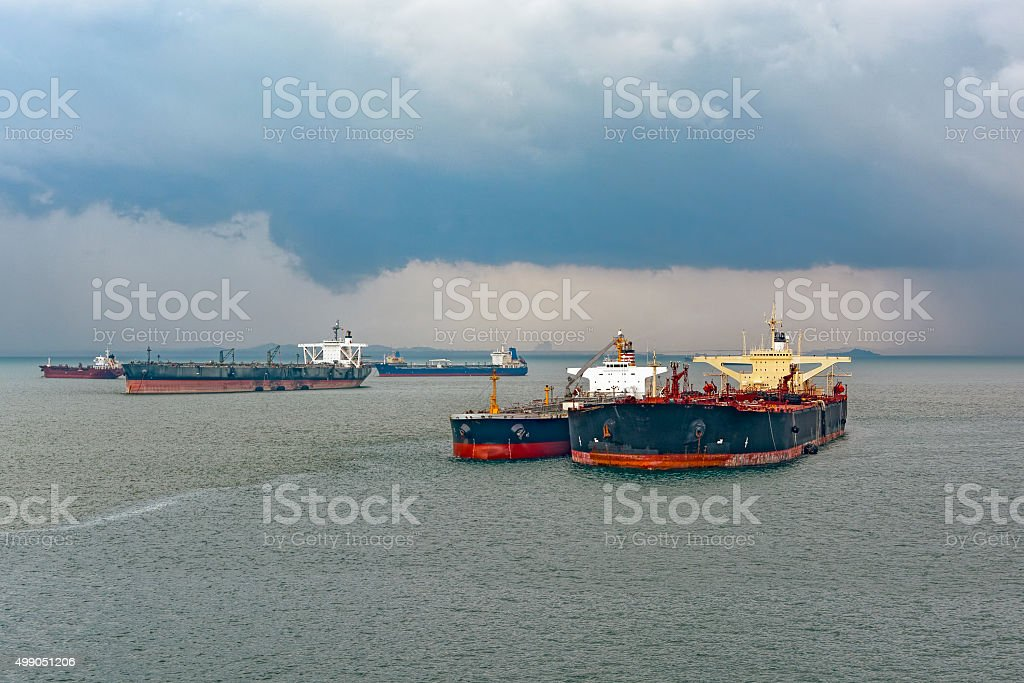 Loading anchored oil supertanker via a ship-to-ship oil transfer stock photo