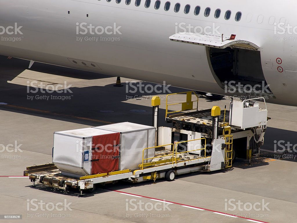 Loading and unloading cargo onto an airplane stock photo