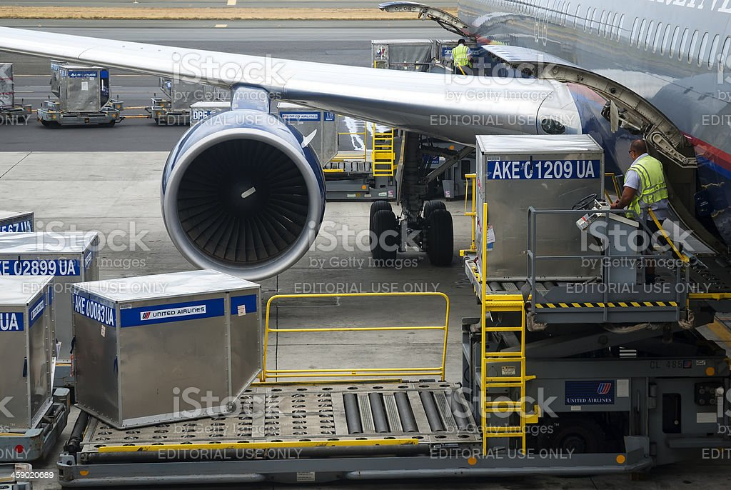 Loading cargo container into a airplane stock photo