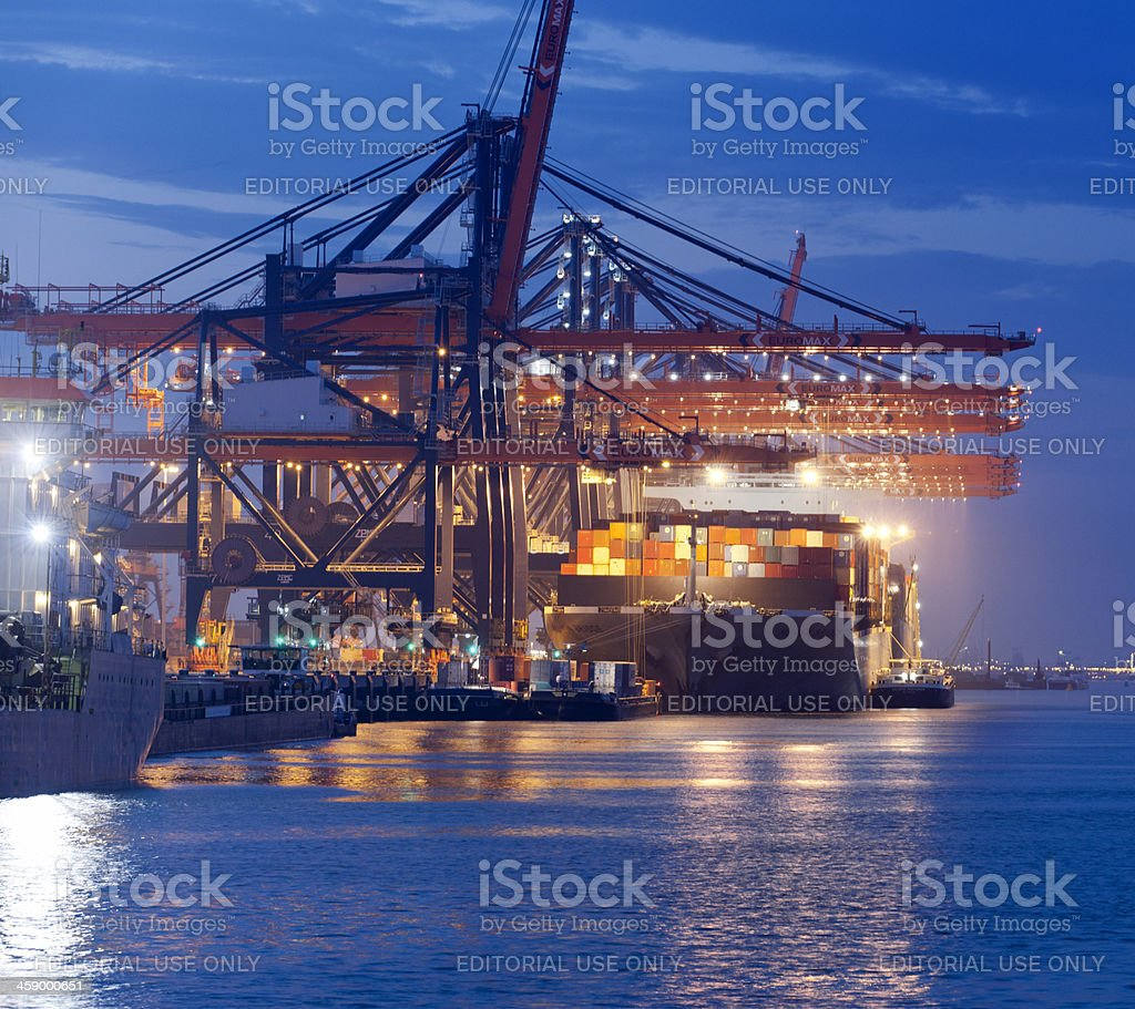 loading cargo container ship in commercial dock at night stock photo