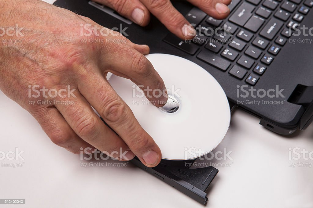 Loading CD into  laptop stock photo