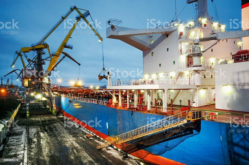 Loading  coal in the hold of cargo ship at night stock photo