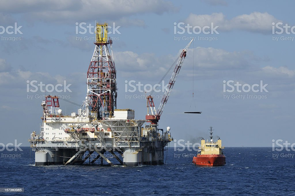 Loading drill pipe to oil rig stock photo