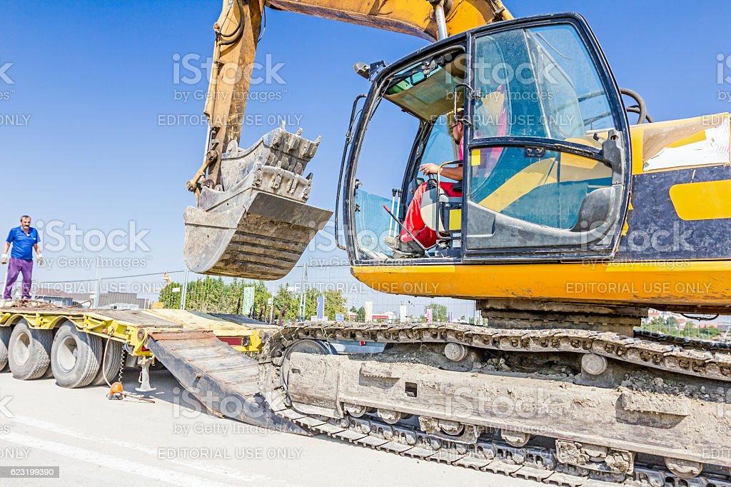Loading excavator on semi trailer stock photo