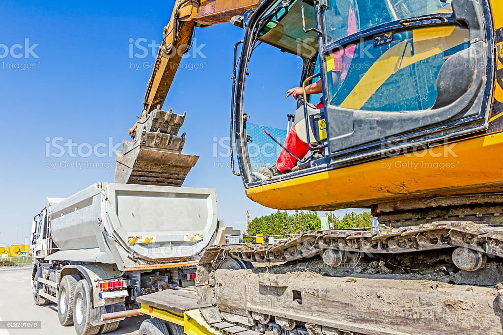 Loading excavator on semi trailer stock photo