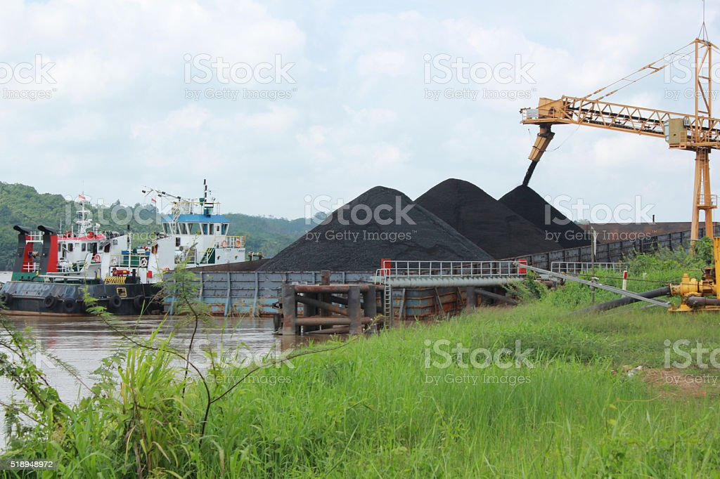loading from conveyor to barge stock photo