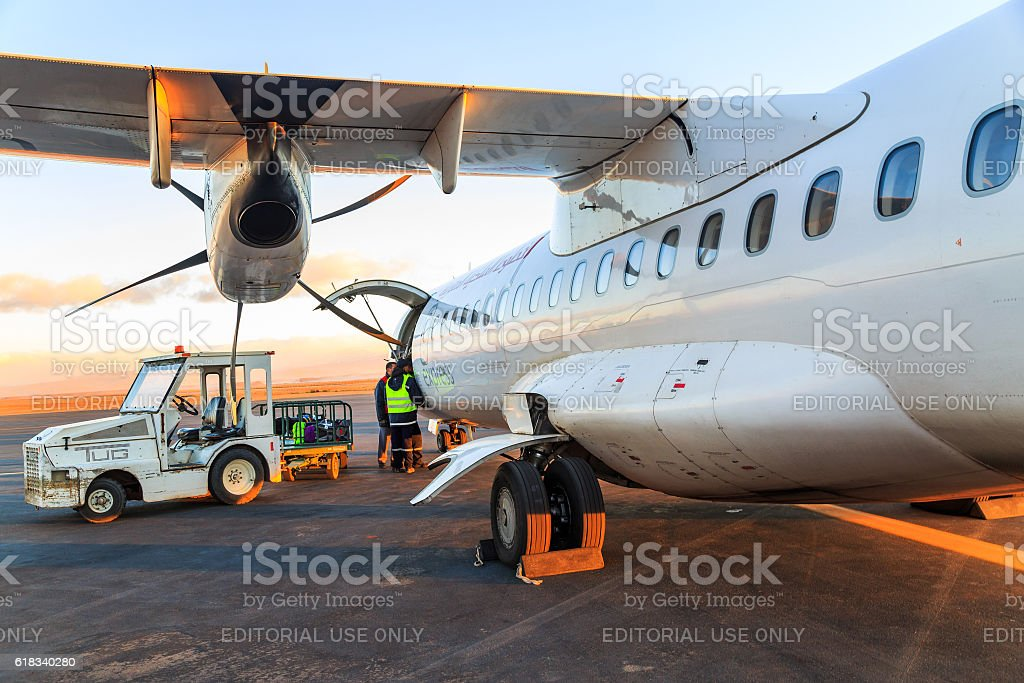 Loading luggage in airplane at daybreak stock photo