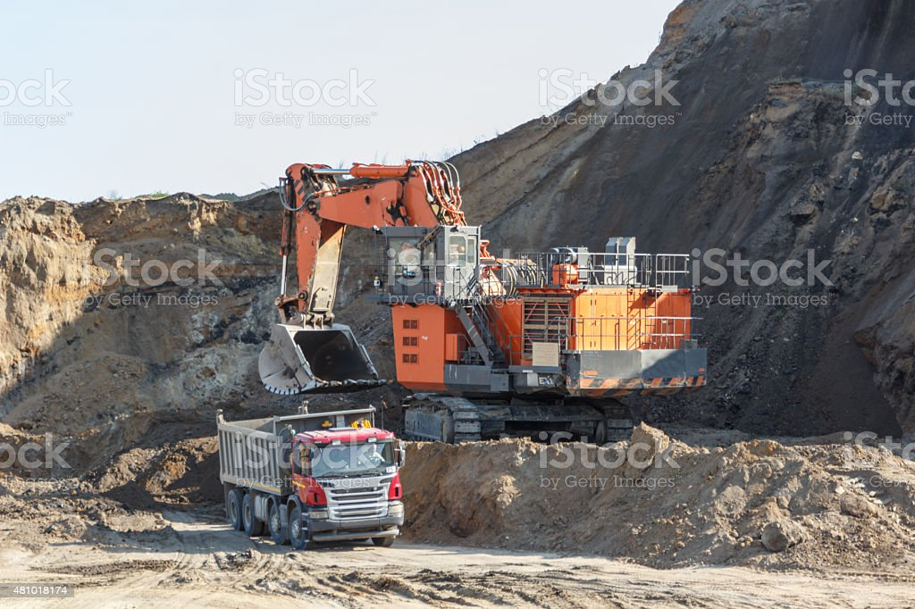 Loading mining trucks an excavator stock photo