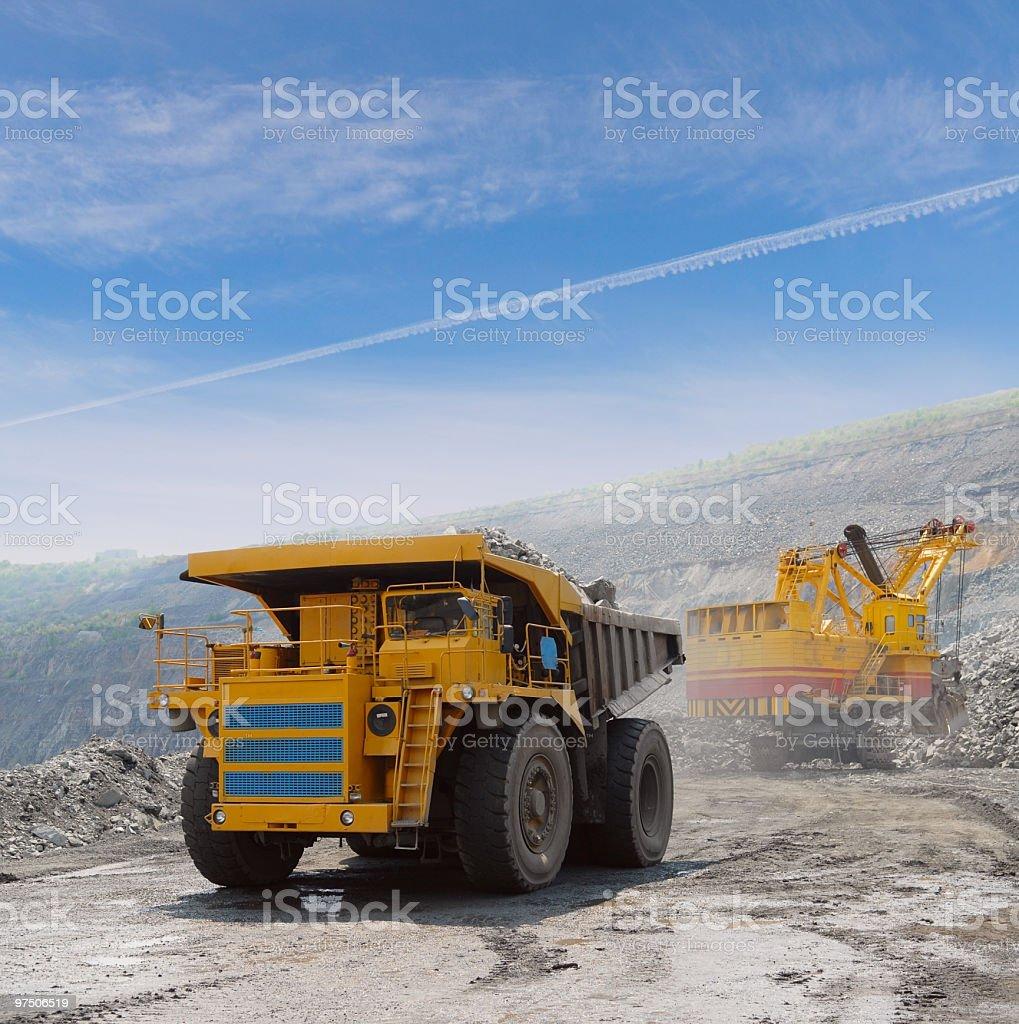 Loading of iron ore into big yellow dump truck stock photo
