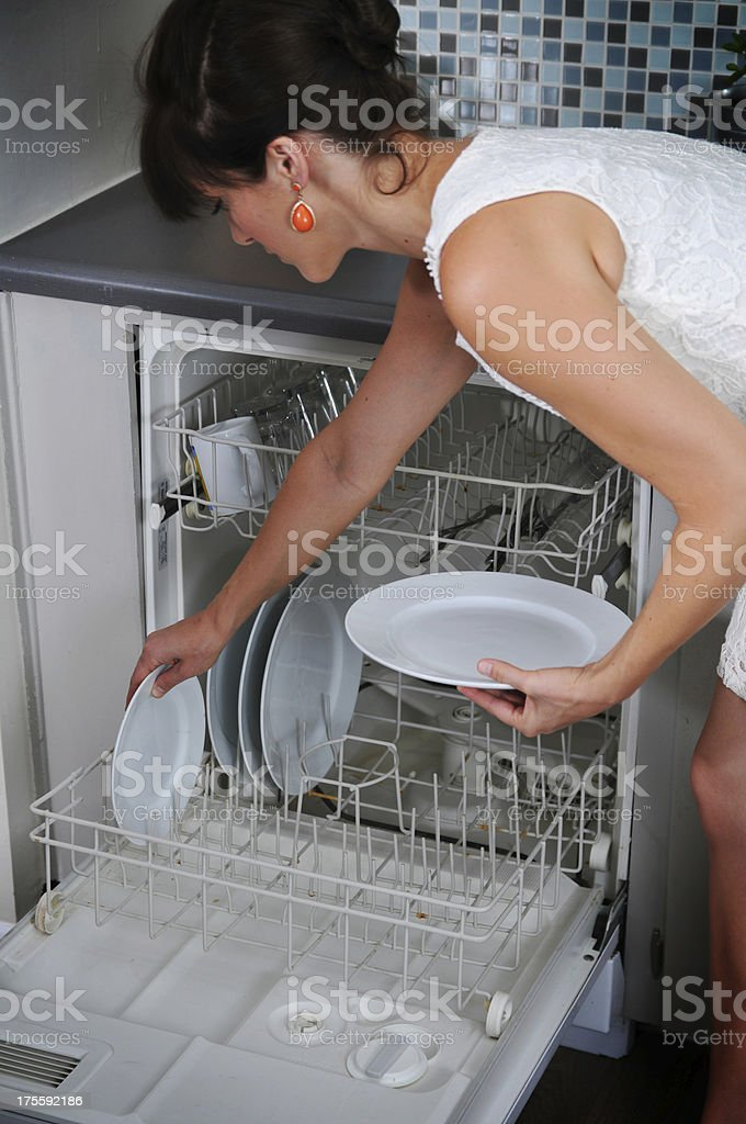 Loading the dishwasher. stock photo