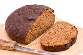 loaf and slice of dark pumpernickel bread