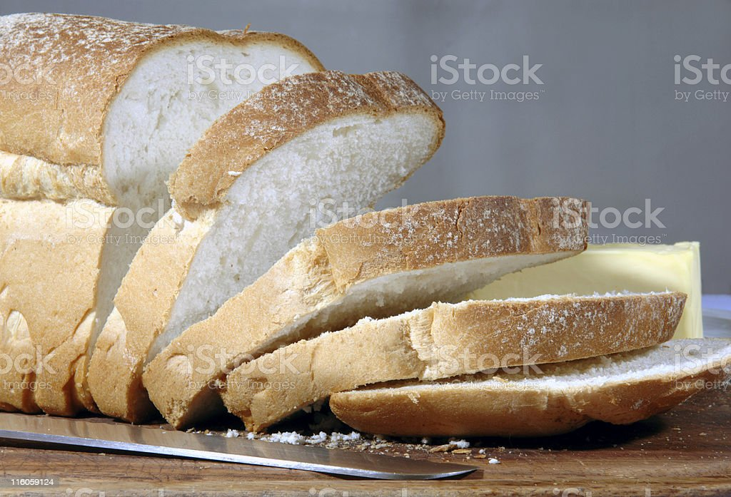 Loaf of bread cut into slices with bread knife stock photo
