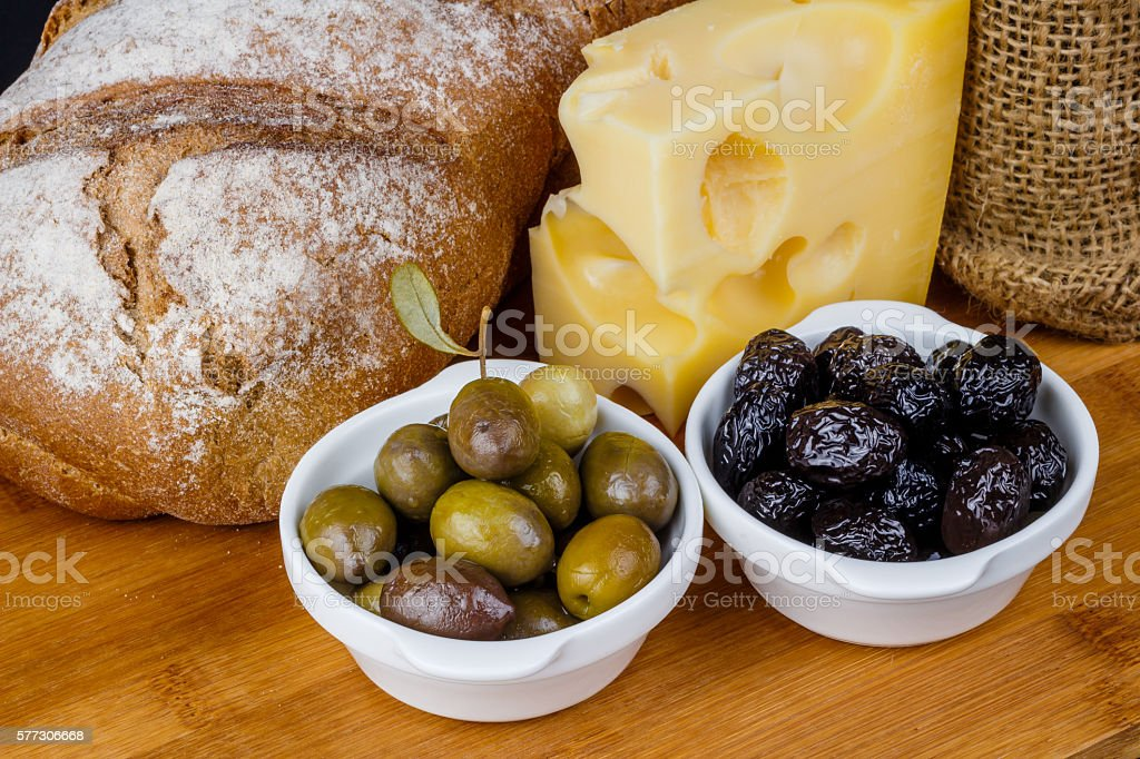 Loaf of bread, piece of cheese, and olives stock photo