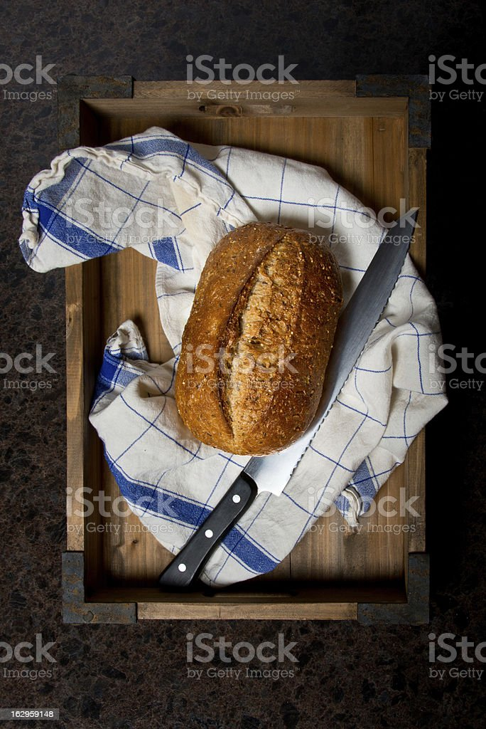 Loaf of Bread with Knife and Kitchen Towel stock photo