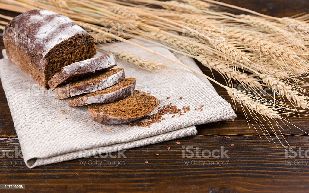 Loaf of rye bread with wheat stalks stock photo