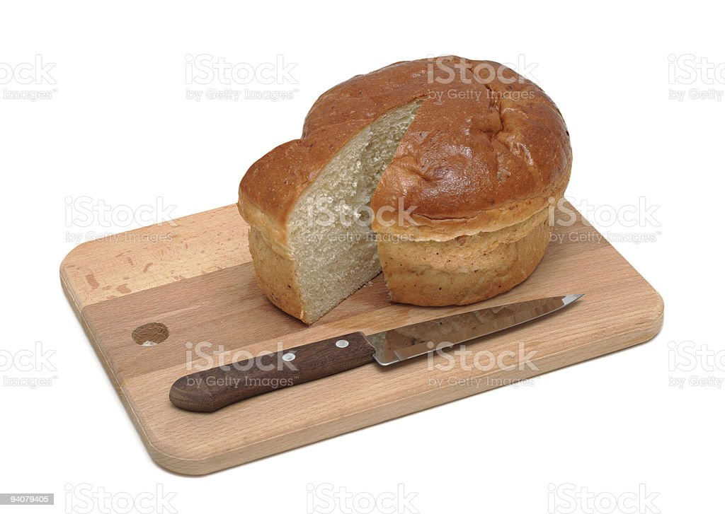 Loaf of sliced bread on a board with knife, isolated royalty-free stock photo