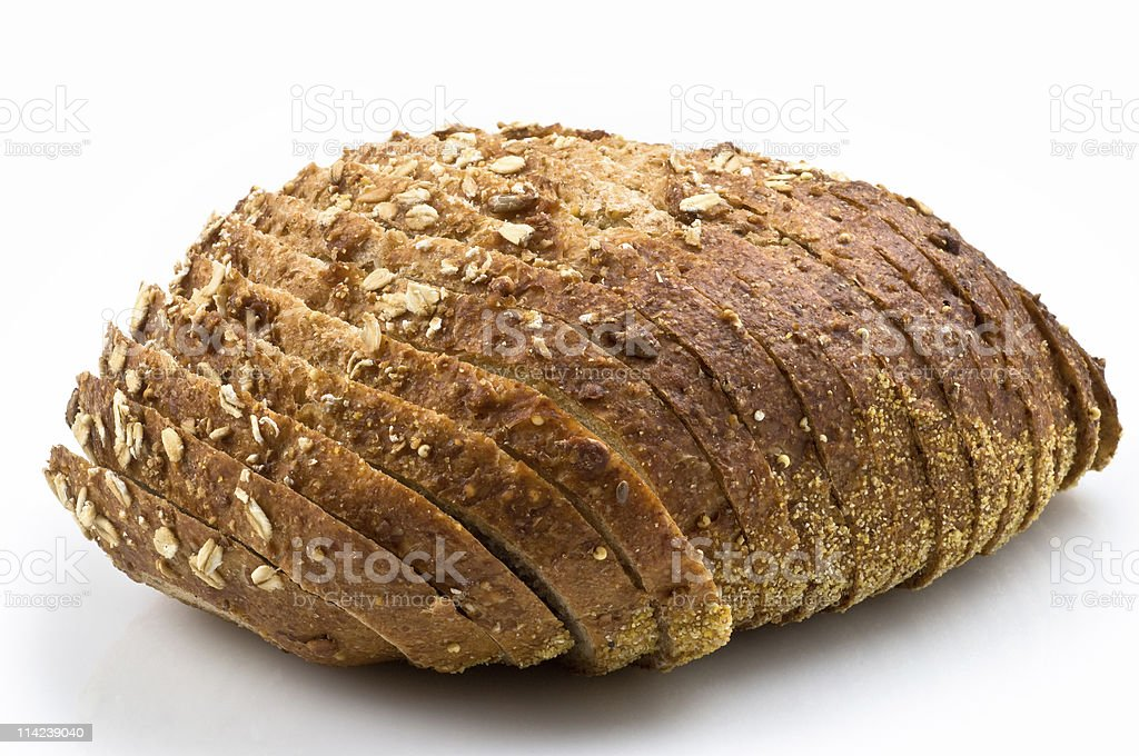 A loaf of sliced whole grain bread topped with grains royalty-free stock photo