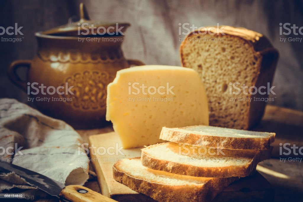 Loaf of sourdough sliced bread on wood cutting board, chunk of cheese, clay dishware, knife, rural kitchen interior stock photo