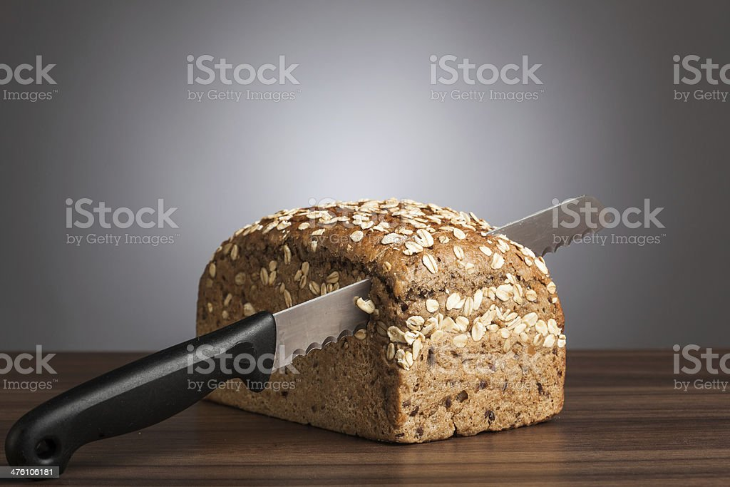 Loaf of wholemeal bread with knife on table royalty-free stock photo
