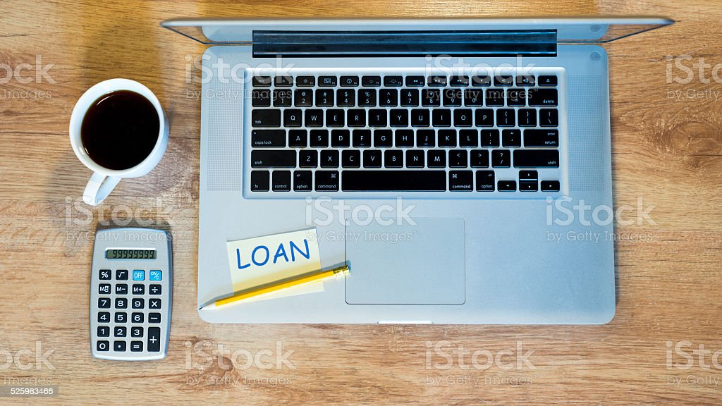 Loan calculation with laptop and calculator while drinking coffee royalty-free stock photo