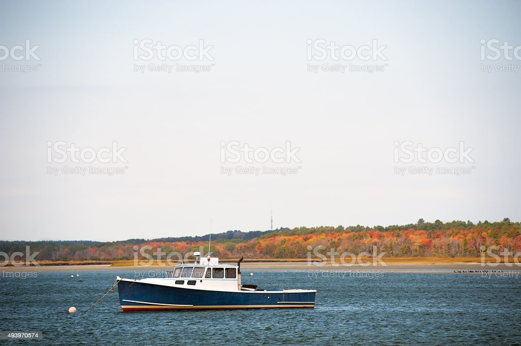 Lobster boat anchored in a Maine harbor in autumn stock photo
