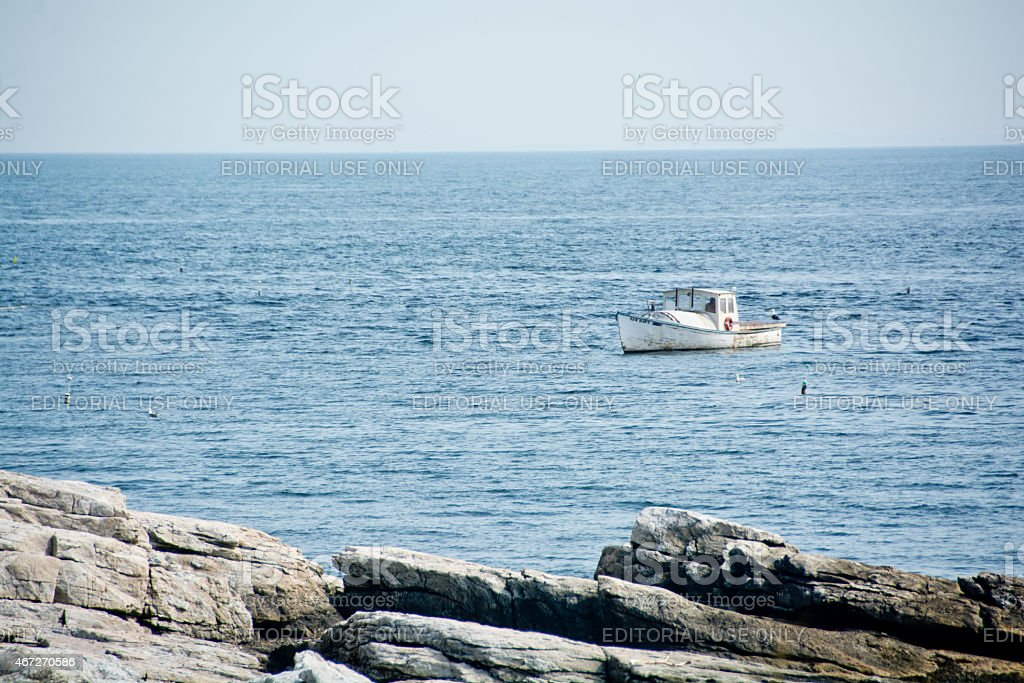 Lobster boat off the rocks stock photo