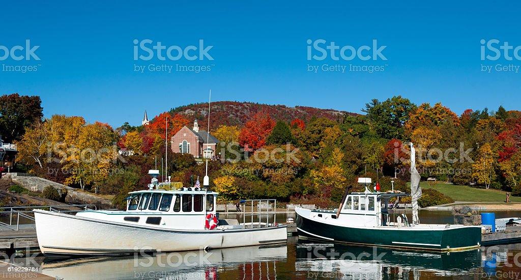 Lobster boats in Camden, Maine Harbor, fall foliage stock photo