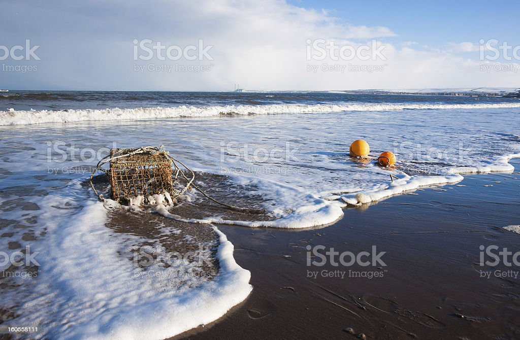 Lobster pot in the surf royalty-free stock photo